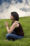 姿势祈祷的坐的妇女 免版税库存照片