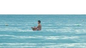 姿势莲花的侧视图人在波浪的明轮轮叶岩石 股票视频
