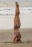 姿势shirshasana 比基尼泳装的一个少妇参与在海滩的瑜伽 免版税库存图片