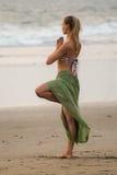 姿势Vrikshasana 比基尼泳装的一个少妇参与在海滩的瑜伽 库存图片