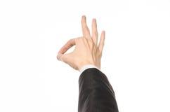 姿态和企业题材:商人在被隔绝的白色背景的一套黑衣服显示与最初人的手势 免版税图库摄影