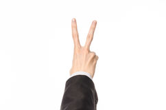 姿态和企业题材:商人在被隔绝的白色背景的一套黑衣服显示与最初人的手势 免版税库存图片