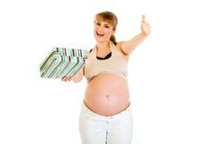姿态愉快的怀孕的显示的赞许妇女 免版税库存照片