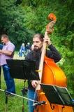 24威严的2017年乌克兰,白色教会 有播放一个低音提琴的胡子的一位年轻音乐家在公园 库存图片