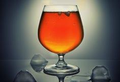威士忌酒、波旁酒、白兰地酒或者科涅克白兰地与冰在灰色背景 免版税库存图片