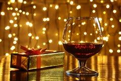 威士忌酒、科涅克白兰地、白兰地酒和礼物盒在木桌上 在轻的背景的庆祝构成 库存图片