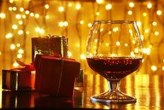威士忌酒、科涅克白兰地、白兰地酒和礼物盒在木桌上 在轻的背景的庆祝构成 免版税图库摄影