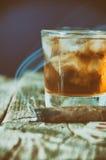 威士忌酒、雪茄和卡片在木背景 图库摄影