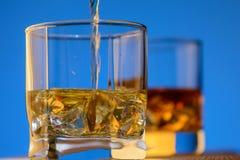 威士忌酒倒与冰的一块玻璃在蓝色背景 免版税库存图片