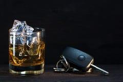 威士忌酒在黑暗的土气木头,概念酒精的玻璃和汽车钥匙 免版税图库摄影