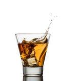 威士忌酒射击与飞溅的在白色 库存图片