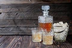 威士忌酒或刻痕从玻璃水瓶到与冰块的一块玻璃里 免版税库存图片