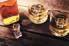 威士忌酒瓶和玻璃与冰在黑暗的木桌上 图库摄影
