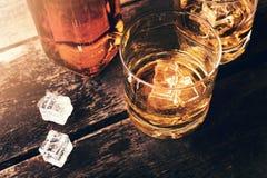 威士忌酒瓶和玻璃与冰块在老木桌上 免版税库存图片