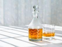 威士忌酒蒸馏瓶和岩石玻璃由窗口 免版税库存图片