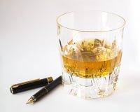 威士忌酒玻璃和钢笔、创造性和生活方式 库存照片