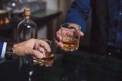 威士忌酒玻璃在手上两供以人员 库存照片