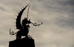 威尔士在剪影的龙雕象,反对冷漠的天空 库存照片