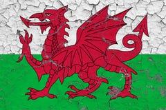 威尔士的旗子在破裂的肮脏的墙壁上绘了 葡萄酒样式表面上的全国样式 库存例证