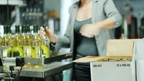 威尔逊, NY,美国:一名未被认出的妇女在箱子采取瓶从传动机的酒并且投入他们 葡萄酒酿造 影视素材