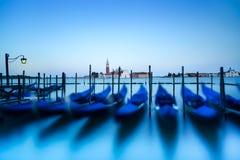 威尼斯、长平底船或者gondole在日落和教会背景的。意大利 库存照片