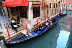 威尼斯。 有报纸的平底船的船夫 免版税库存图片