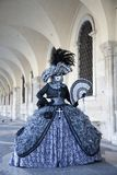 威尼斯在一套五颜六色的黑和灰色服装的狂欢节在共和国总督宫殿下威尼斯意大利欧洲的拱廊的形象和面具 库存图片