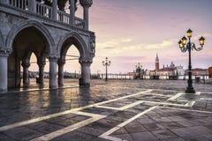 威尼斯地标在黎明、圣马可广场,共和国总督宫殿和圣G 免版税库存图片