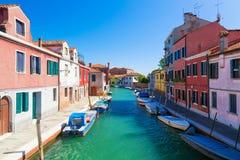 威尼斯地标, Murano海岛运河、五颜六色的房子和小船在夏日期间与蓝天在意大利 威尼斯盐水湖 免版税图库摄影