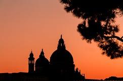 威尼斯大教堂在日落的圆顶剪影 令人惊讶的灼烧的天空 图库摄影