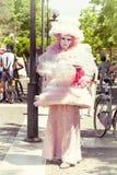 威尼斯式桃红色服装,游行在街道的美丽的女孩 免版税库存图片