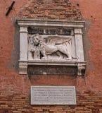 威尼斯式狮子的石浅浮雕在威尼斯武库的墙壁上的  圣马克狮子是城市的标志 库存照片