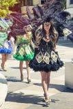 威尼斯式黑服装,游行在街道的美丽的女孩 图库摄影
