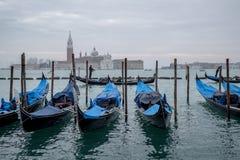 威尼斯意大利 荡桨在大运河的平底船的船夫一艘长平底船在威尼斯,有圣乔治海岛的在背景中 库存照片
