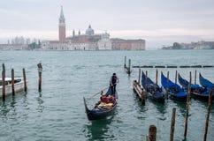 威尼斯意大利 荡桨在大运河的平底船的船夫一艘长平底船在威尼斯,有圣乔治海岛的在背景中 免版税库存照片
