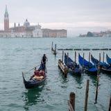 威尼斯意大利 荡桨在大运河的平底船的船夫一艘长平底船在威尼斯,有圣乔治海岛的在背景中 库存图片