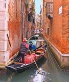 威尼斯水运河,有长平底船的意大利人在一条狭窄的运河运载的游人荡桨  免版税图库摄影