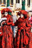 威尼斯狂欢节、两名妇女有红色服装的和面具 免版税库存图片