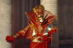威尼斯狂欢节在一套五颜六色的红色和金服装和面具威尼斯意大利图 免版税库存图片