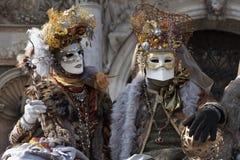 威尼斯狂欢节在一套五颜六色的金子和棕色服装图并且掩没威尼斯意大利 免版税库存照片