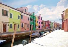 威尼斯,意大利, 2015年4月13日 Burano海岛,本机多彩多姿的房子  在渠道的银行的咖啡馆 Burano islan 库存照片