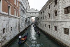 威尼斯,意大利:10月04日:有游人乘驾的长平底船在10月04日的著名Ponte dei Sospiri下在威尼斯,意大利 库存照片