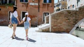 威尼斯,意大利- 2018年7月7日:一个少妇和一个孩子女孩相同牛仔布总体的,短裤,步行通过街道 影视素材