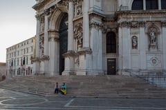 威尼斯,意大利- 2017年10月7日:圣玛丽亚della致敬大教堂,人们坐寺庙的步 免版税库存图片
