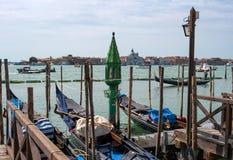 威尼斯,意大利- 2018年5月08日:在码头的长平底船 一盏古色古香的绿色灯,富有地装饰用玻璃和镀金面 免版税库存照片