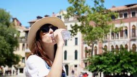 威尼斯,意大利- 2018年7月7日:太阳镜和帽子的一个少妇清楚地喝着,从瓶的干净的高山水 影视素材