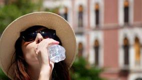 威尼斯,意大利- 2018年7月7日:太阳镜和帽子的一个少妇清楚地喝着,从瓶的干净的高山水 股票录像