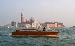 威尼斯,意大利- 2017年10月13日:小船在大运河的水中 在背景中是在海岛上的大教堂 库存图片