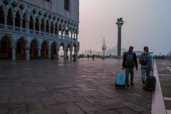 威尼斯,意大利- 2017年10月6日:带着手提箱的两个游人去在圣马可广场,早晨 免版税库存照片