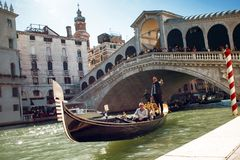 威尼斯,意大利- 2017年10月7日:平底船的船夫在大运河, Rialto桥梁在背景中漂浮 免版税库存图片